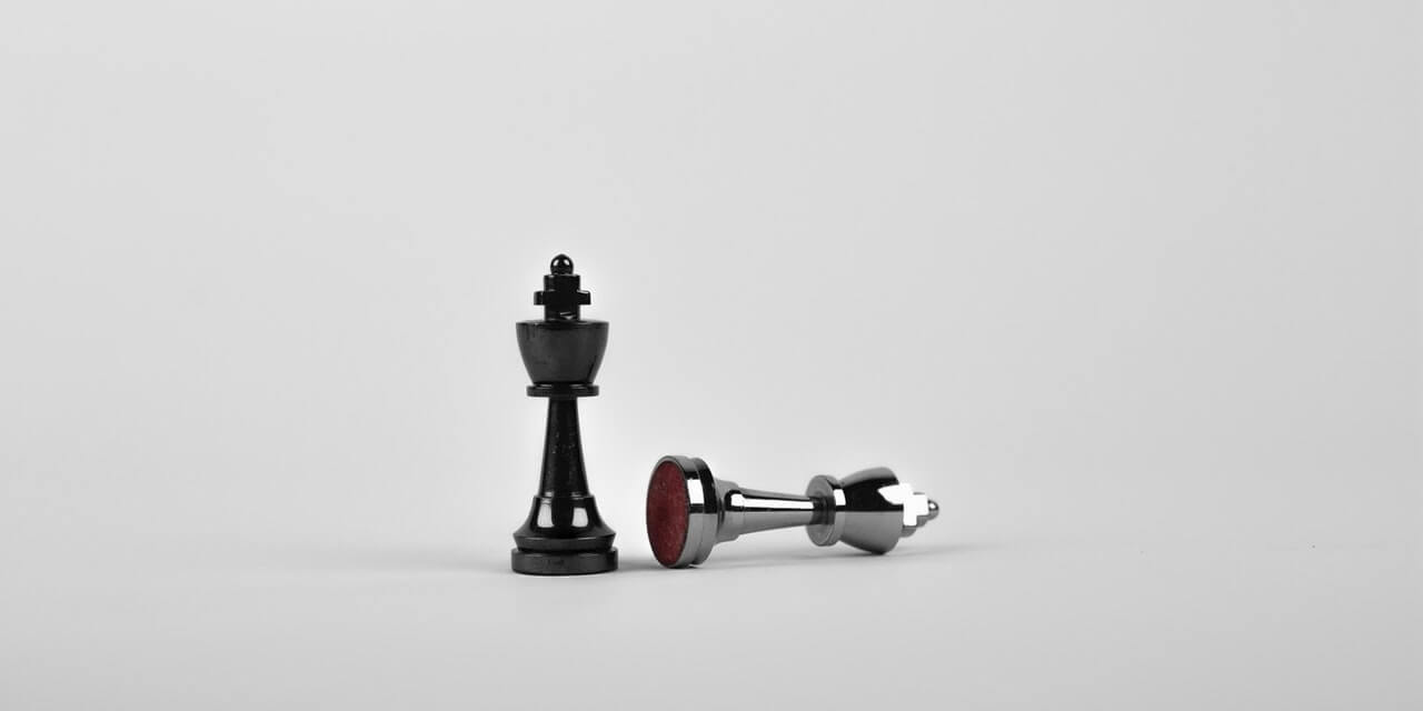 black-chess-piece-stood-next-to-beaten-white-chess-piece