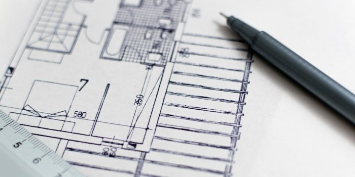 black-pen-resting-on-architects-drawings
